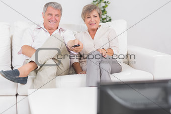 Old couple watching TV with legs crossed
