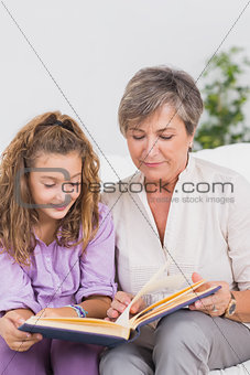 Little girl and her grandmother reading a book