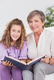 Little girl and her grandmother looking at the camera with a book