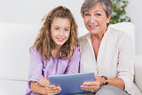 Little girl and her grandmother looking at the camera with tablet pc