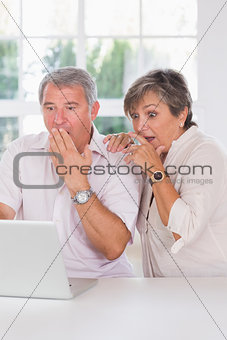 Old couple shocked in front of a laptop