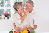 Old man tasting vegetable held by wife
