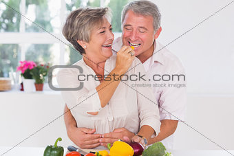 Old man tasting vegetable held by wife