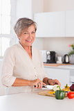 Old woman cutting vegetables on a cutting board with a smile