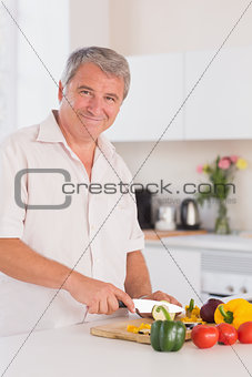 Old man smiling and chopping vegetables