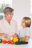 Grandmother cutting vegetables looking at grandson