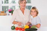 Grandmother cutting vegetables with her grandson