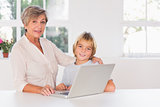 Granny and child looking camera with a laptop