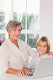 Grandmother and child looking camera with a laptop