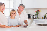 Child and grandparents looking at the camera with a laptop in front