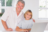 Grandfather and child looking at the camera with smile in front of laptop