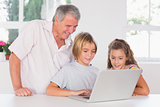 Grandfather and children looking at laptop together