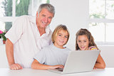 Grandfather and children looking at the camera with laptop in front
