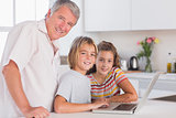 Grandfather and children looking at the camera together with laptop in front