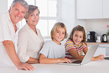 Grandparents and childrens looking at the camera together with laptop in front