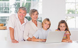 Children and grandparents looking at the camera together with laptop in front