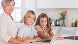 Children and grandmother looking at the camera together with laptop in front