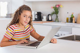 Smiling child looking at the camera with laptop