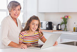 Grandmother and little girl looking at the camera with laptop