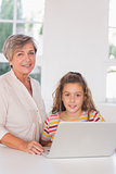 Smiling grandmother and child looking at camera together with laptop