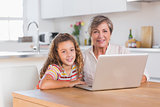Child and granny looking at the camera with laptop
