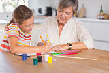 Little girl drawing with her grandmother focused