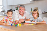 Grandfather and her grandchildren smiling at the camera with drawings