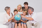 Family looking at globe on couch
