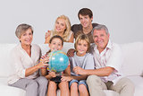 Family portrait looking at camera with a globe