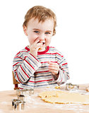 happy young child nibbling dough in white background