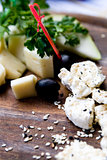 Splitting a solid tasty goat cheese with sesame seeds and herbs