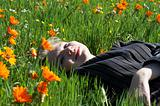 Blonde woman lying in a field of flowers