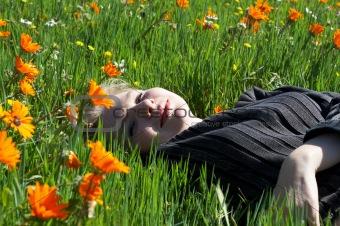 Blonde woman lying in a field of flowers