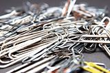 Paper clips lying in a pile on a desk