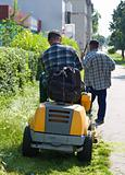 two men are cutting grass