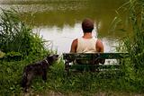man is sitting on bench on lake