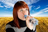 Redhead girl drinking water