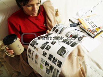 a young woman is reading a new car booklet
