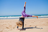 Young girl doing cartwheel at beach
