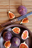 plate with fresh figs and old knife on straw background