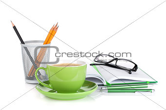 Green coffee cup, glasses and office supplies