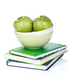 Green apples in fruit bowl and books