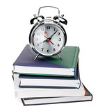 Alarm clock on notepads and books
