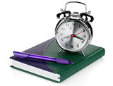 Alarm clock and pen on notepad
