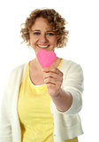 Woman showing pink paper heart to camera