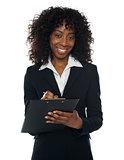 Pretty corporate woman writing on clipboard