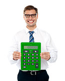 Male executive displaying green calculator