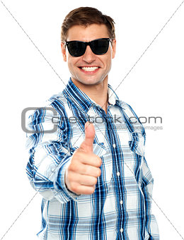 Smart young guy showing thumbs up