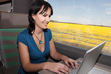 woman in a train computing laptop computer smiling