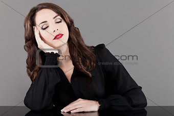 Beautiful woman sitting at table with eyes closed